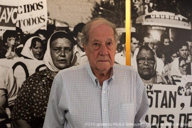 Robert Cox está de pie en el Espacio de Memoria y Derechos Humanos. Está parado en Detrás suyo hay una gigantografía que muestra a Madres de Plaza de Mayo protestando por la aparición de sus hijos.