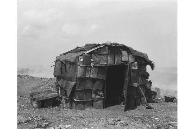 Una fotografía de una casa precaria tomada por Harry Grant Olds
