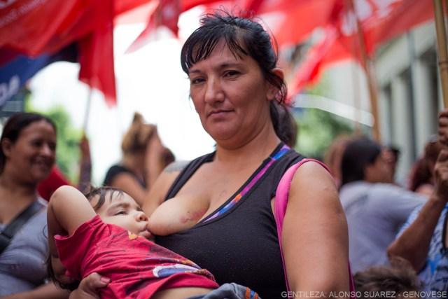 Mujer amamantando a su hijo durante un manifestación.