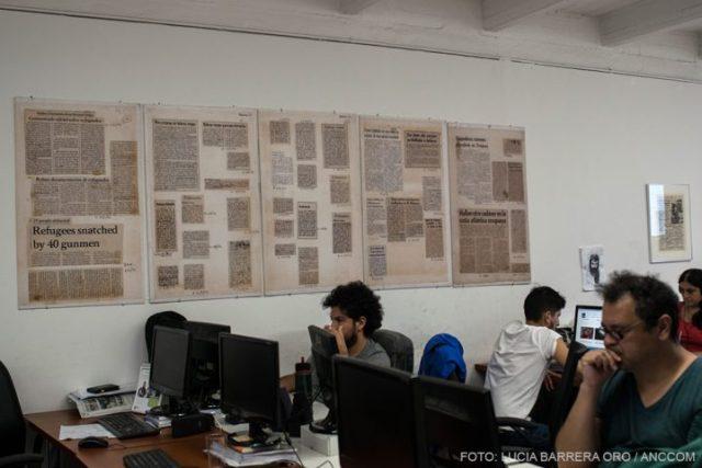 Trabajadores de Tiempo Argentino sentados deltante de las computadoras mientras en la pared se presentan recortes de diarios.