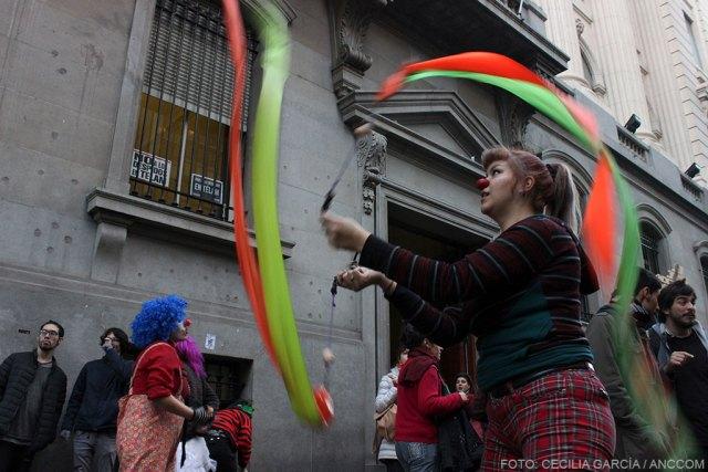 Mujer vestida de payaso haciendo actividad con cintas en la calle.