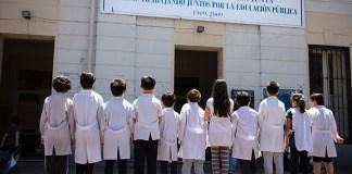 "Alumnos con guardapolvo frente a la puerta de la Escuela Nº 3 D.E. 7º ""Primera Junta"""