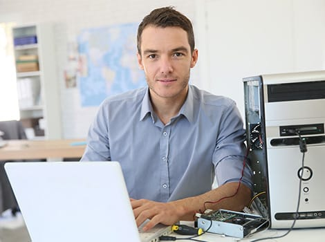 smiling man works on computer, representing IT threat remediation