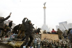 Anti-government protesters throw stones towards Interior Ministry members and riot police in Independence Square in central Kiev