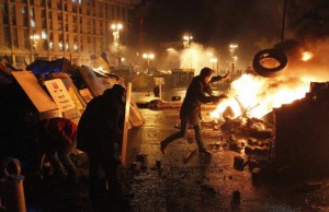 An anti-government protester throws a tire during clashes with riot police at the Independence Square in Kiev