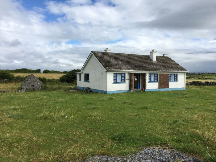 A white cottage house in the Irish countryside.