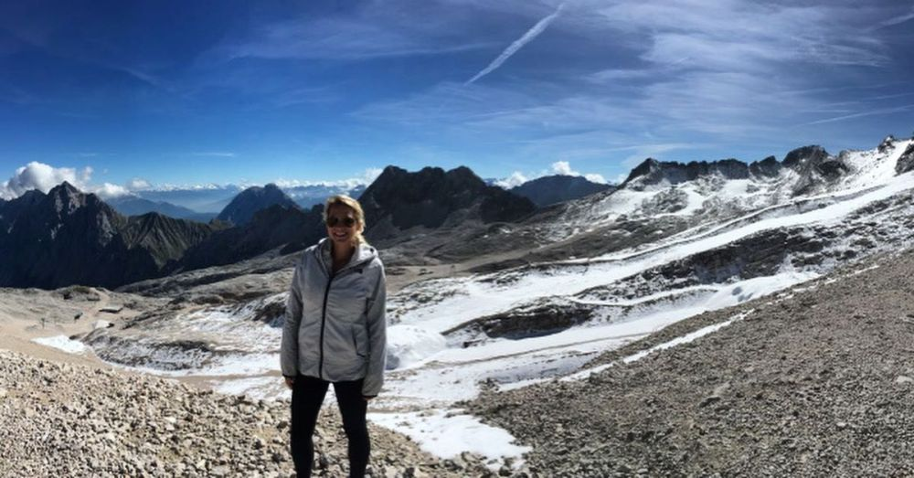 A woman posing with the mountains in the background at the Zugspitze in Germany.