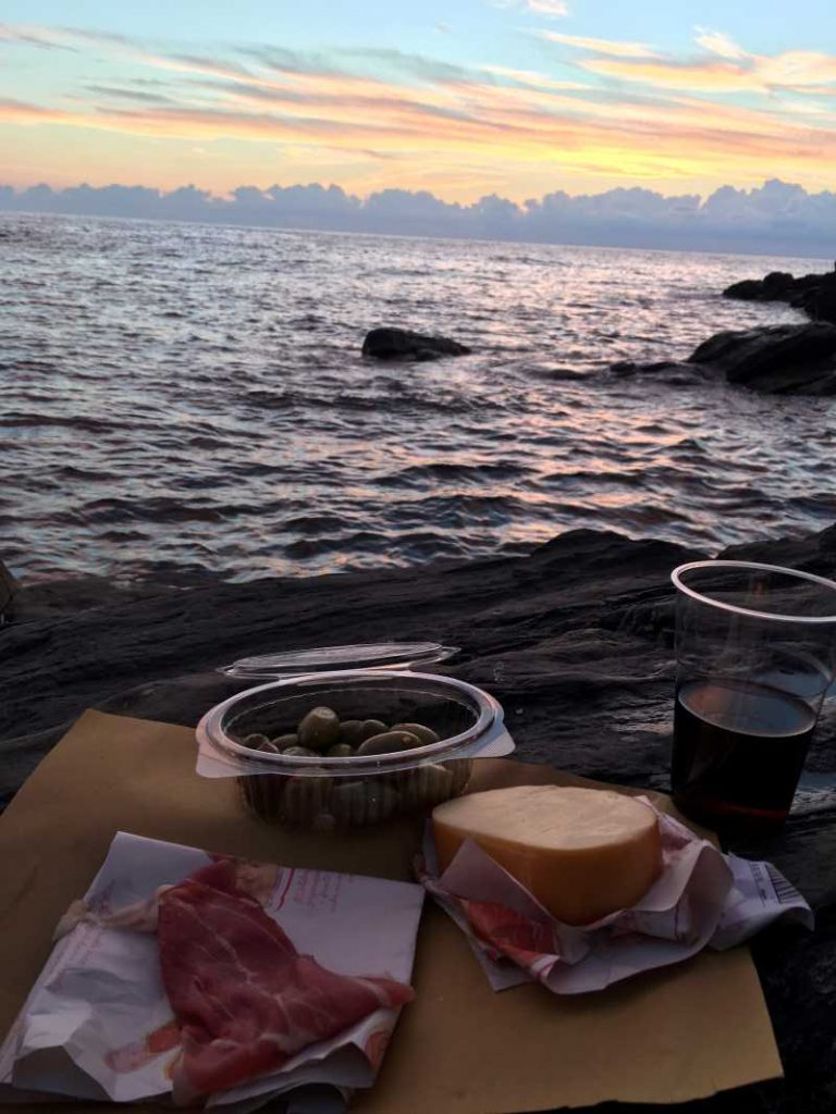 A photo of a cheese and meat tray on the beach. The ocean and sky are in the background.