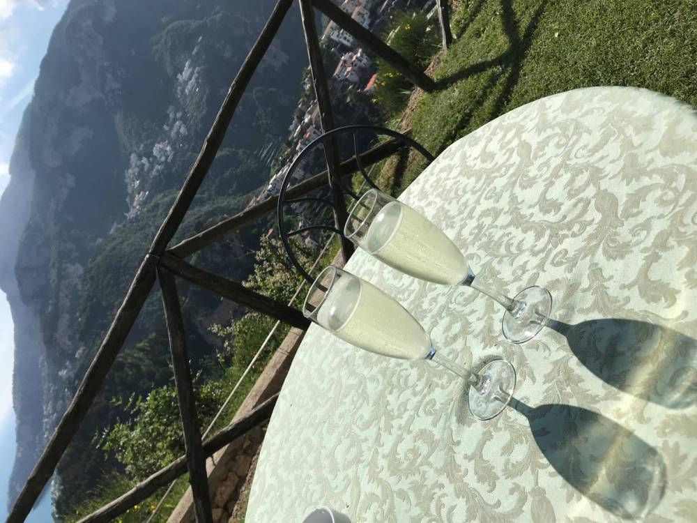 A photo of two glasses of sparking wine sitting on a table overlooking the town of Scala from Villa Cimbrone, one of the two well-known gardens in Ravello.