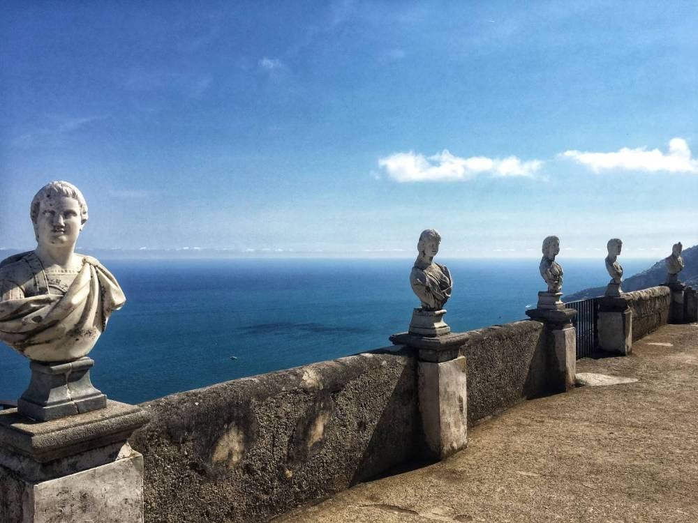 A photo from the Villa Cimbrone garden terrace with five marble bust statues. The blue coastline is in the distance.