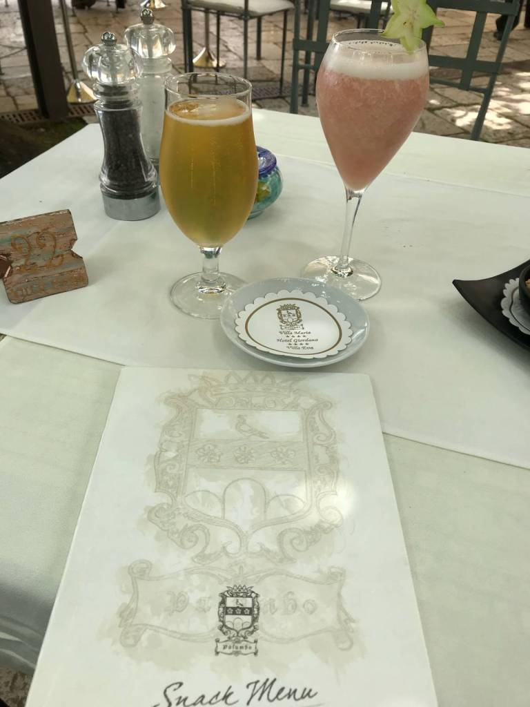 A photo of two glasses on the table of restaurant, Villa Maria, one of the restaurants recommended in Ravello. One glass is a beer, and the other glass is a bellini.