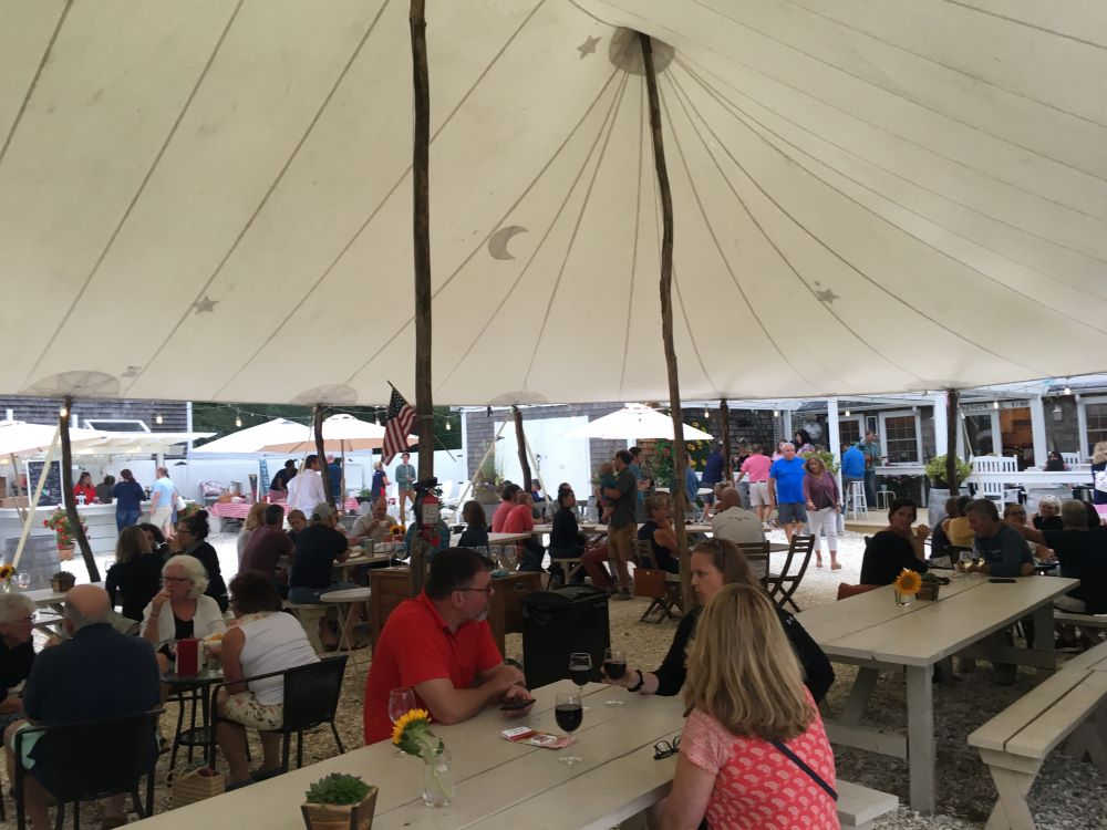 People sitting at picnic tables at the Cape Cod Winery.
