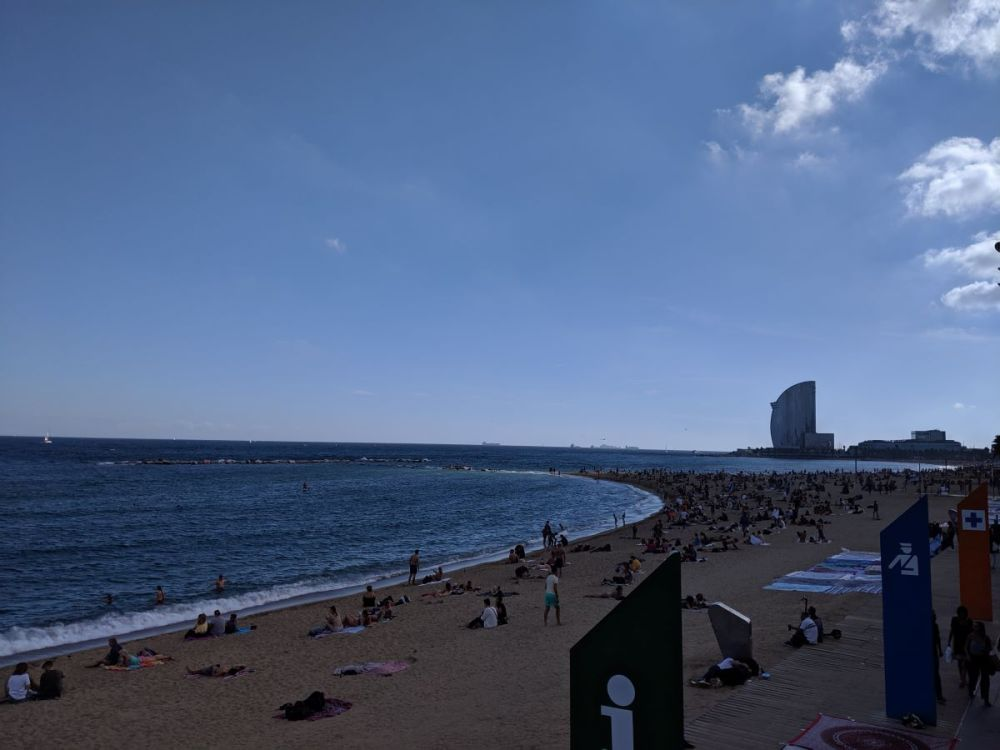 The beaches in Barcelona with people laying on the sand.
