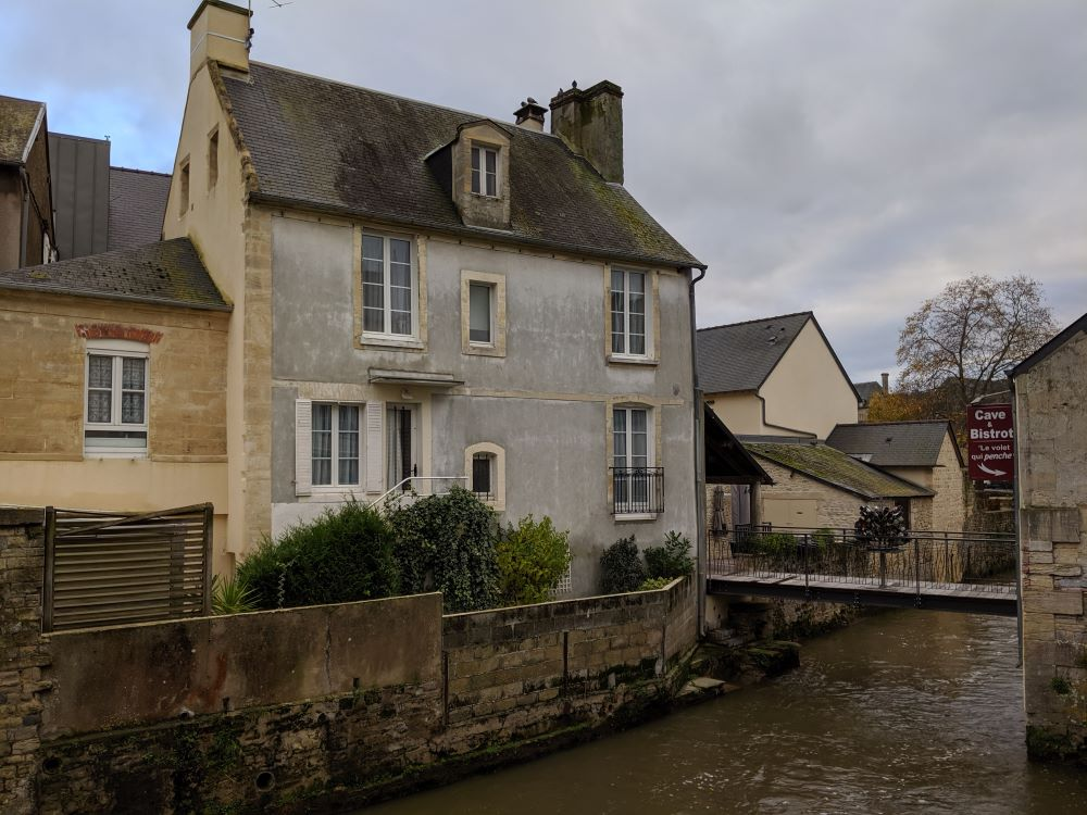 House line the river bank that runs through the Old Town in Bayeux France