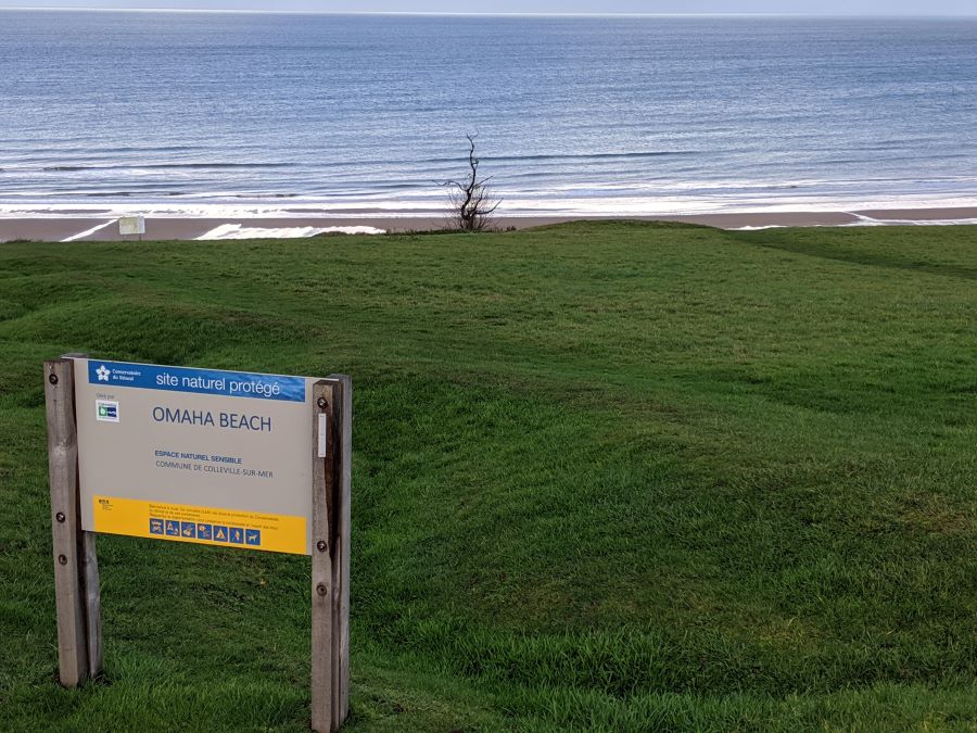 A sign that says Omaha Beach sits just infront of the ocean and sandy beach.