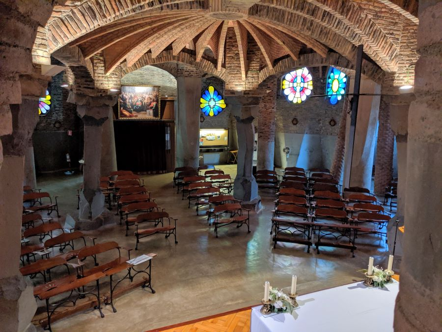 The crypt of Colonia Güell filled with stained glass windows and church pews.