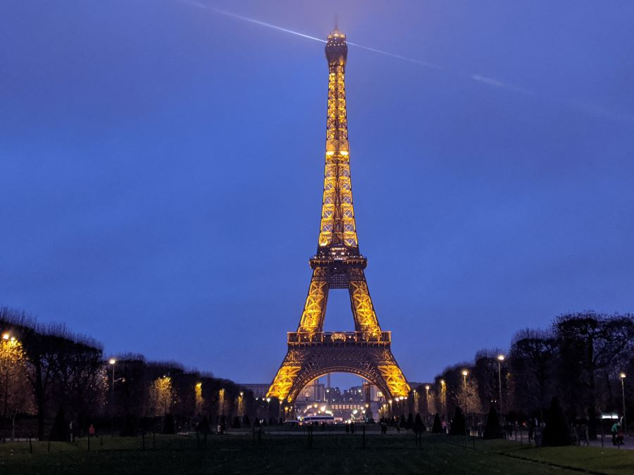 The Eiffel Tower in Paris lit up at dusk.