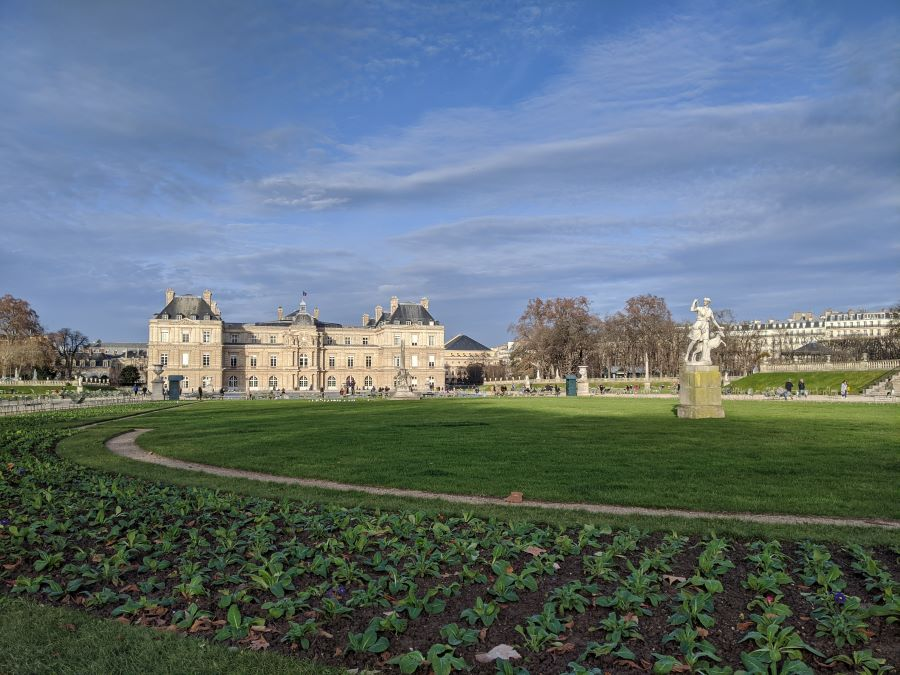 The green grass of Luxembourg Gardens with a statue and building in the middle.