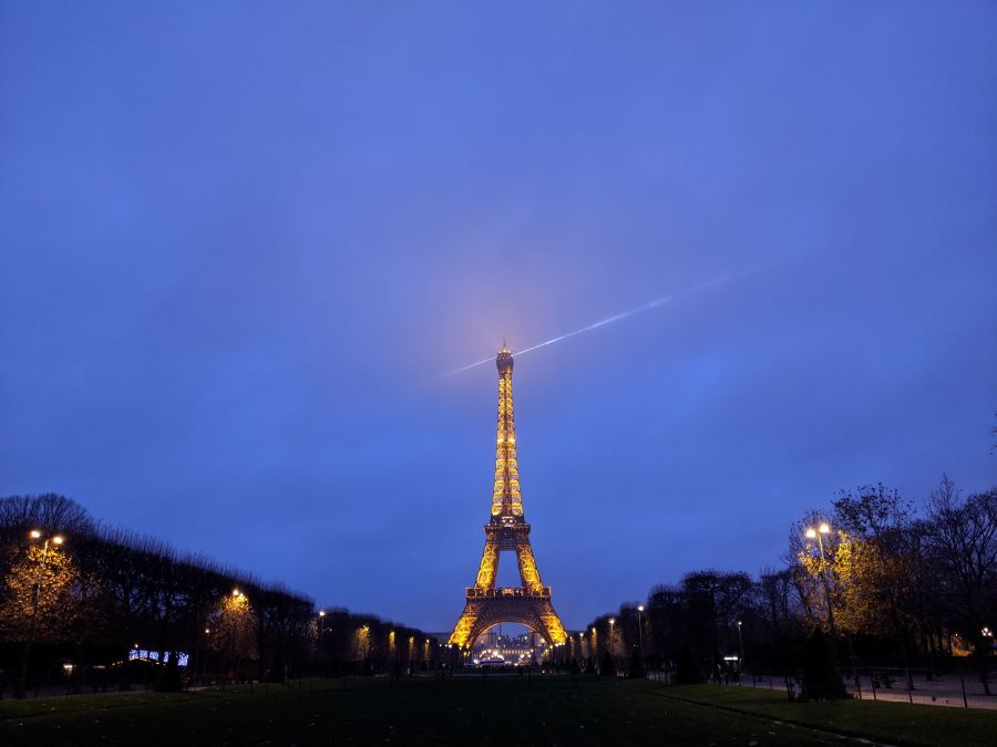 The Eiffel Tower in Paris lit at dusk. The sky line is a purple/blue color.
