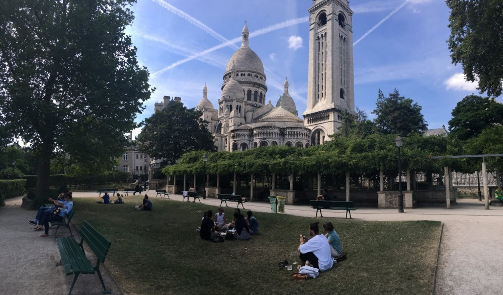 Several people lounging in the garden outside the stone church, Sacre-Coeur in Paris.