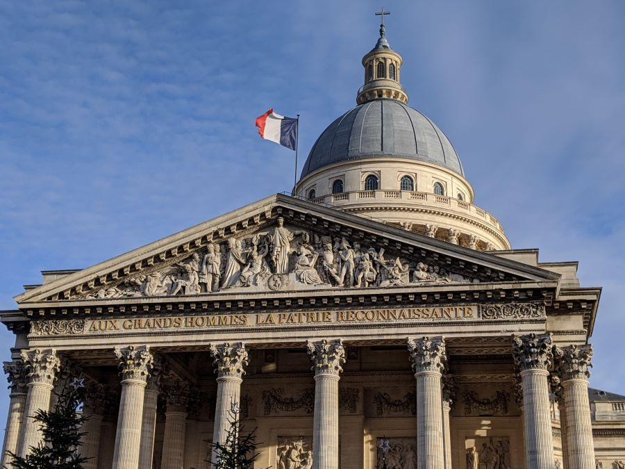 A large stone church with six columns, a large blue dome, and the French flag (red, white and blue colors) flying on top.
