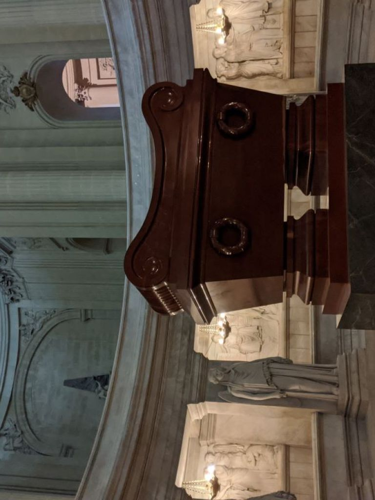 The oak wood tomb of Napoleon with several marble statues surrounding it.