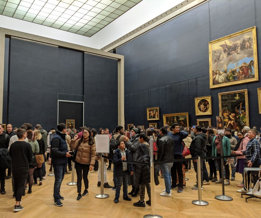 Dozens of people standing in line to see the Mona Lisa.