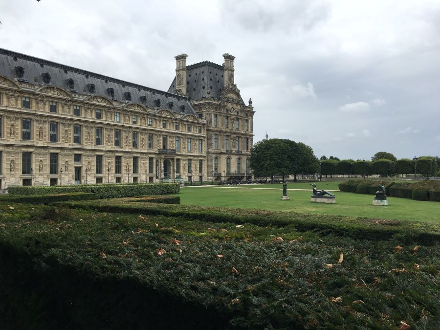 Lush grass and hedges in the gardens outside the Louvre Museum, which is partly seen in the background.