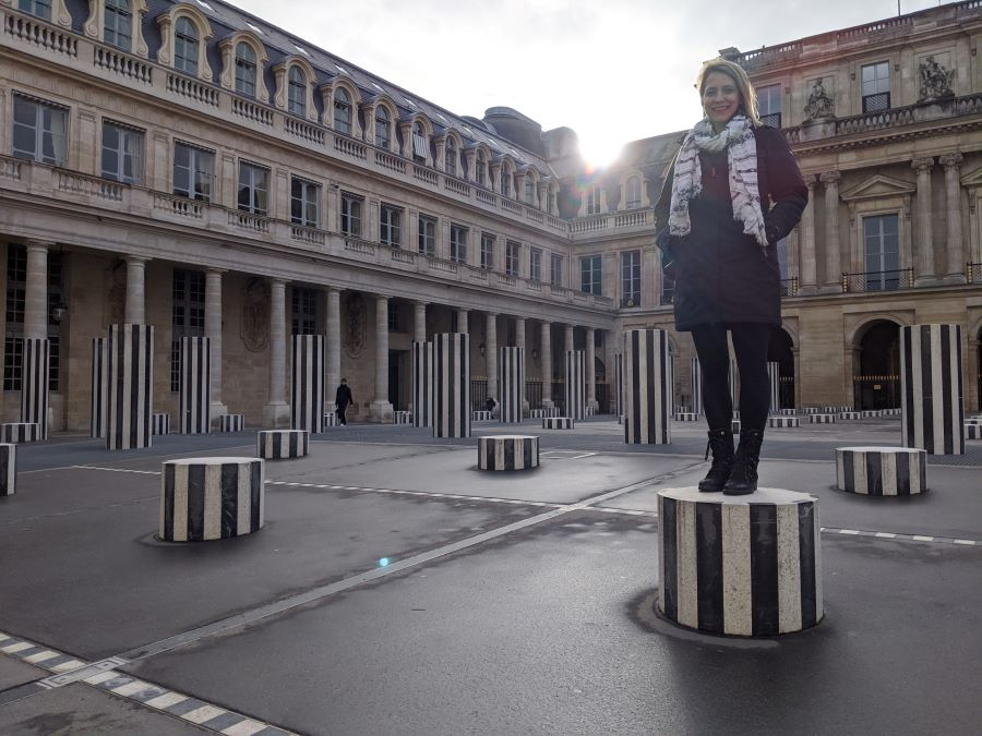 A young woman standing on a short black and white column in a square in Paris.