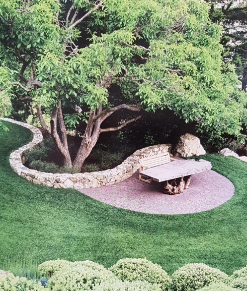 beautiful stone bench in a backyard of a limestone french farmhouse