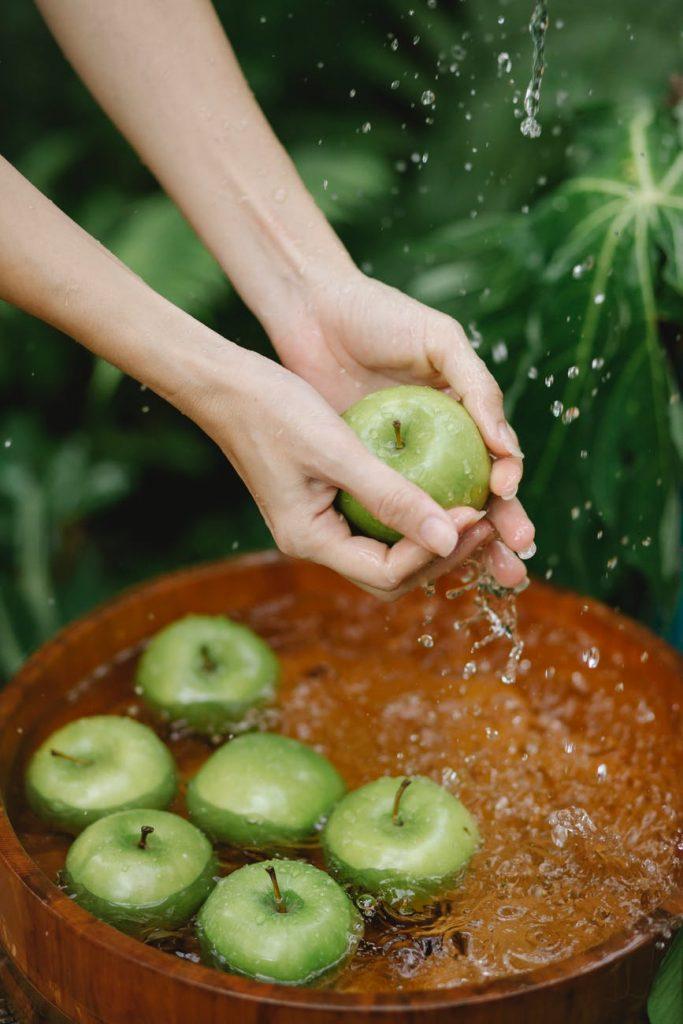 crop woman washing green apples in wooden basin in garden