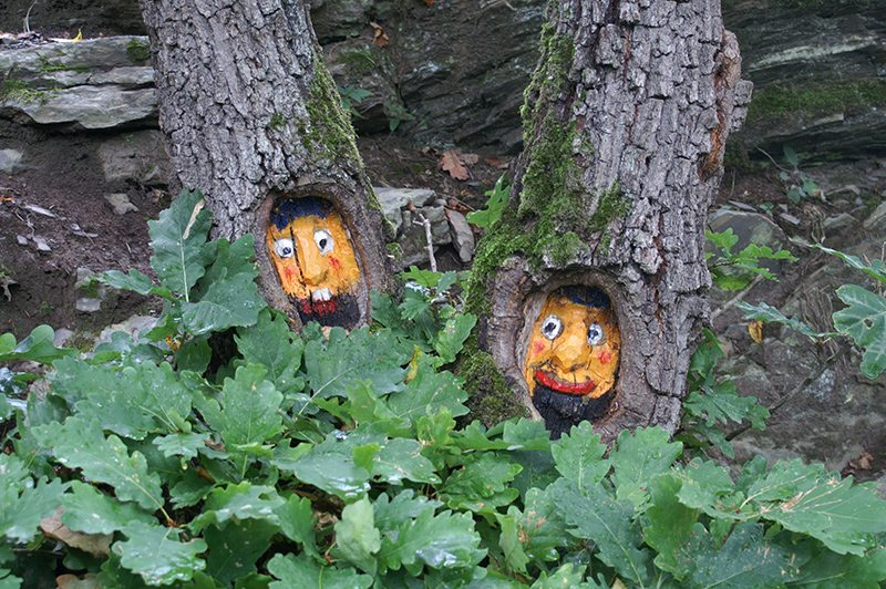 Erstaunte Blicke auf den Wanderer: Geschnitzte und bemalte Baummasken am Wegrand des AV1