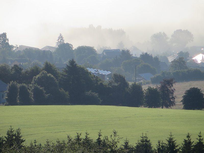 Das unter uns gelegene Mörschied schält sich langsam aus dem Morgendunst (Foto: Hans-Joachim Schneider)