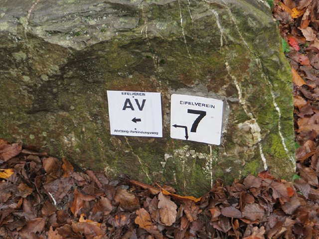 Wegmarkierungen AV und 7 an einer Sitzbank: Gehört der Vergangenheit an: der alte AV ist nun offiziell zur 5. Etappe des AhrSteigs gekürt worden (Foto: Hans-Joachim Schneider)