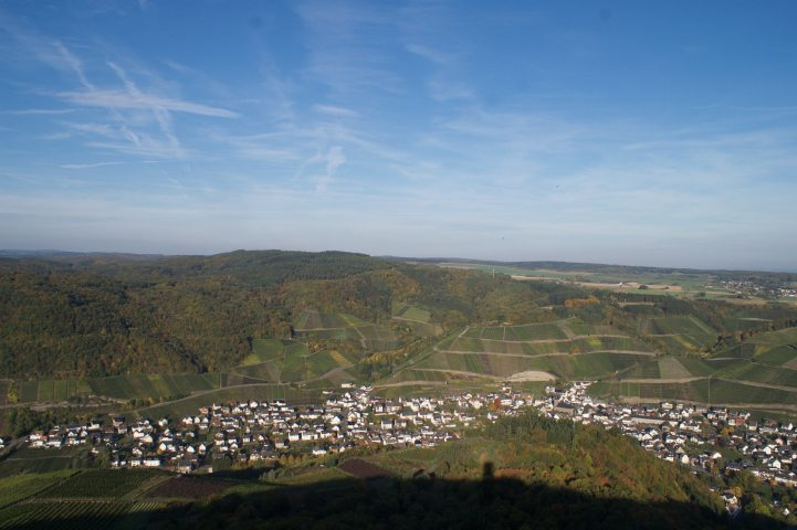 Blick vom Krausbergturm auf den Winzerort Dernau, dahinter die Weiberge, darüber spannt sich blauer Himmel