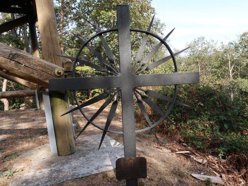 handgeschmiedetes Kreuz aus Stahl am Fuß des hölzernen Aussichtsturmes