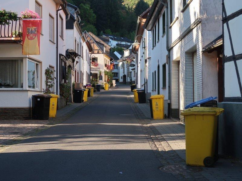 Im Morgenlicht liegt die Straße durch das Weindörfchen Rech. Gelbe und graue Mülltonnen stehen Spalier