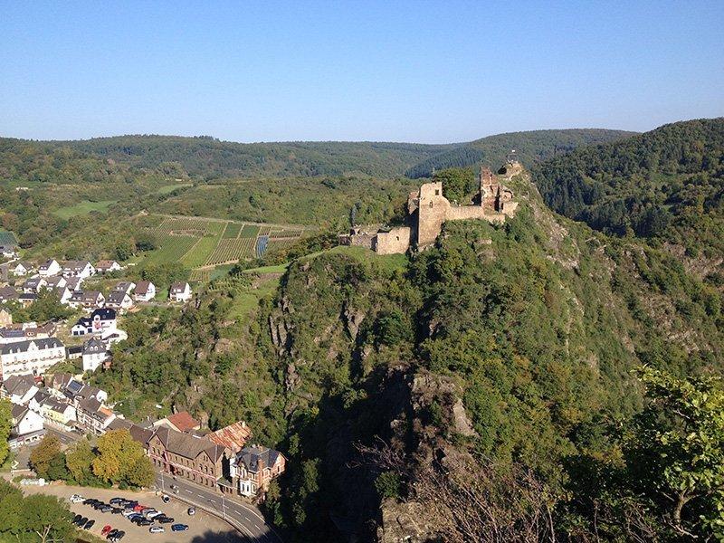 Altenahr im Tal, darüber die Ruinen der Burg Are auf einem grünen Hügel