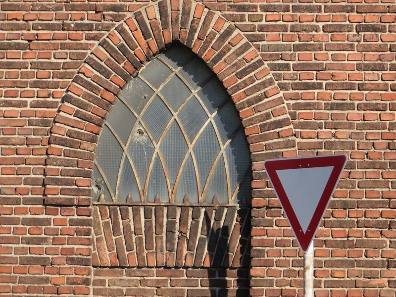 Straßenschild vor einer Backsteinmauer.