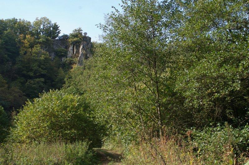 Fast zugewachsene Wege, Gebüsch, blauer HImmel, ein Felsvorsprung, an dem der Blick hängenbleibt.