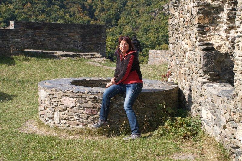 Mauerreste, ein alter Brunnen und meine Schwester, die sich auf dem Brunnenrand ausruht.