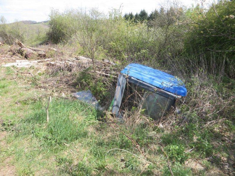 Die Fahrerkabine eines Traktors, einfach abgeladen, wird langsam vom Gras überwuchert.