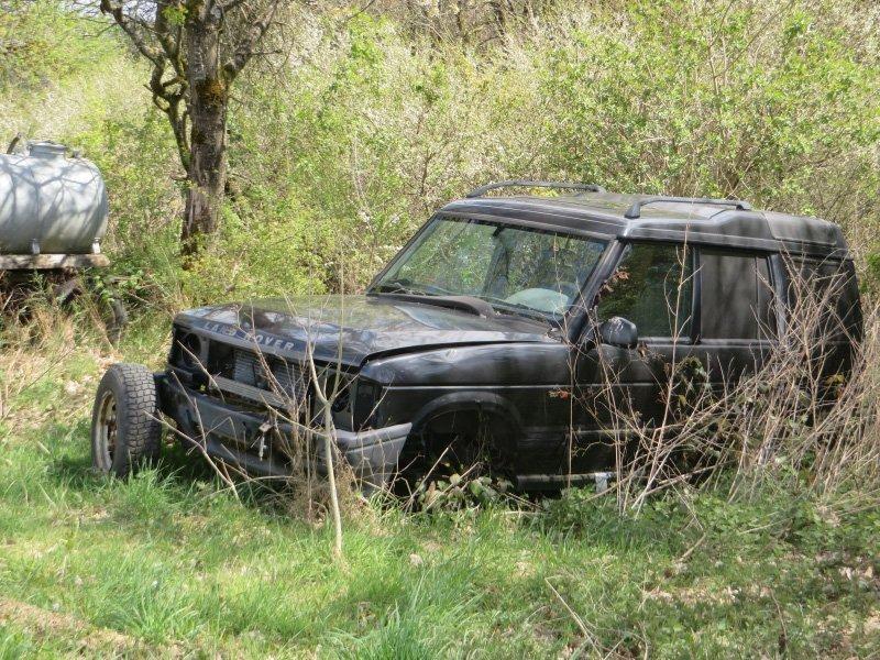 Ein großer SUV, ein Range Rover verrottet am Waldrand.