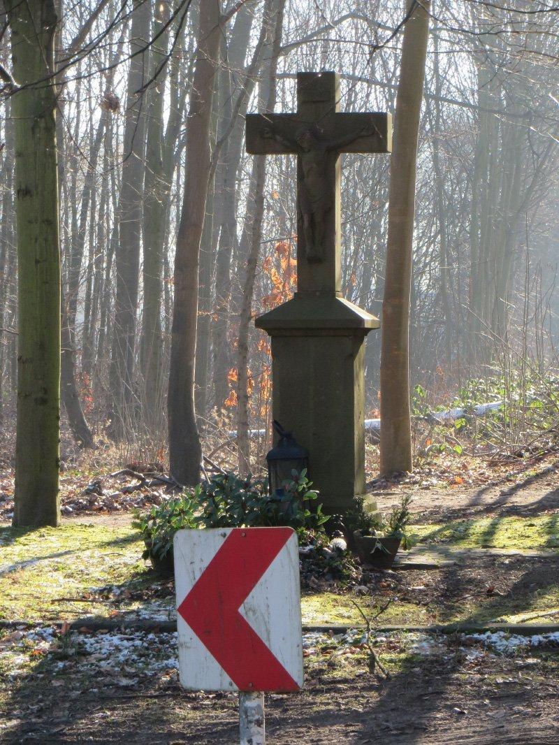 Sandsteinkreuz im Wald, von der Sonne beschienen
