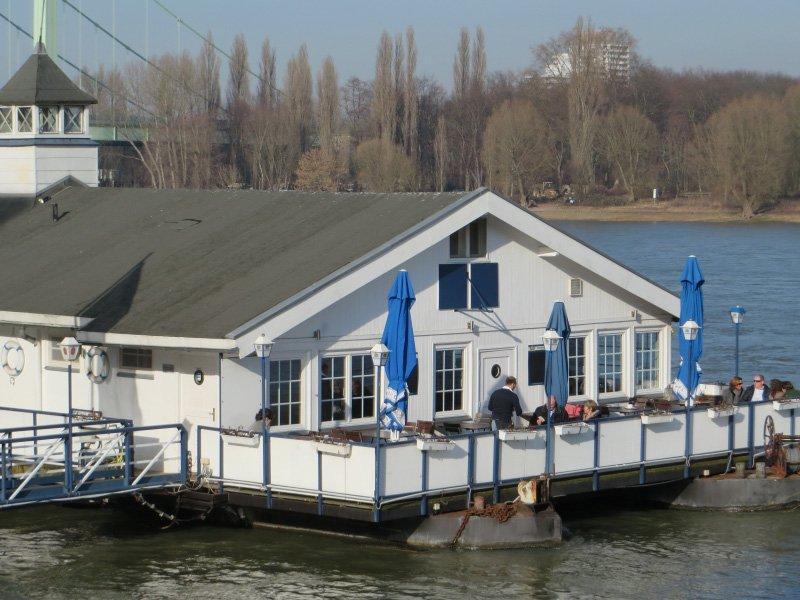 Restaurantschiff am Rheinufer, in der Sonne draußen sitzen und Kaffee trinken