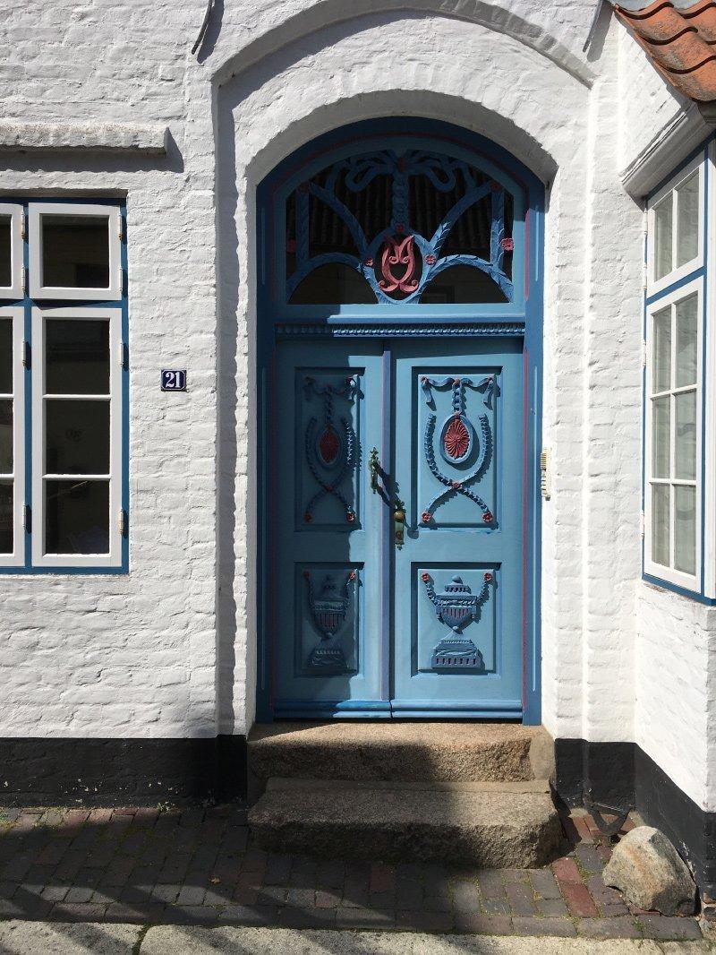 Blaue Haustür mit roten und dunkelblauen Zierelementen: das macht die Schönheit der Altstadt Husums aus