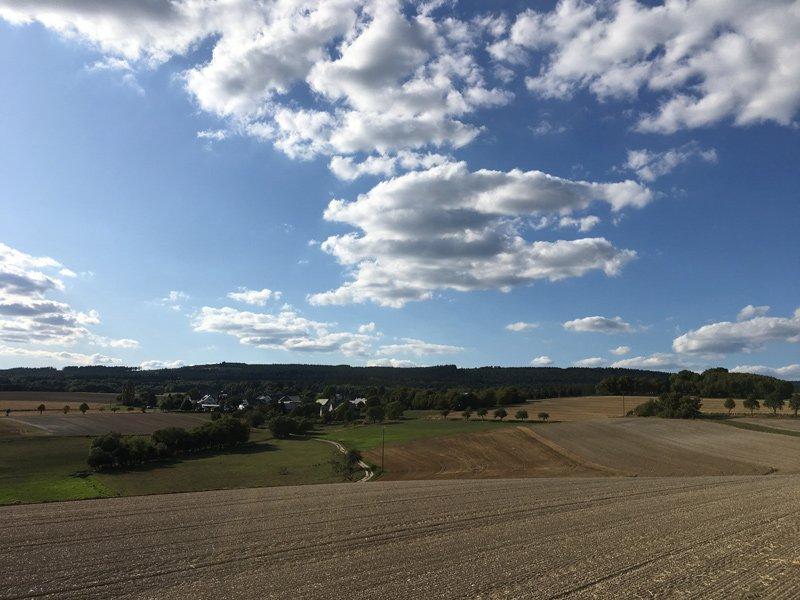 Umgepflügtes Ackerland erfreut das Herz der Bauern, grüner Wald am Horizont das Herz des Wanderers