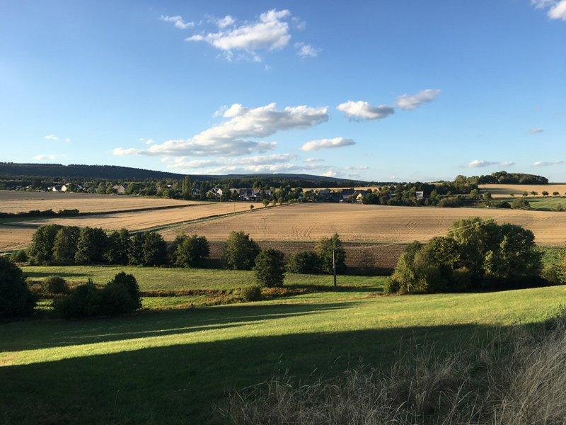 Blick über die Weite der Landschaft: Wiesen im Vordergrund, Gebüschstreifen, Ackerland, eine Dorfsilhouette, darüber blauer Himmel