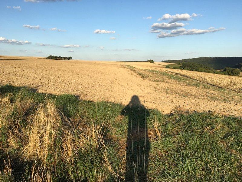 Überblick über die Ackerlandschaft, im Vordergrund ein Schattenselfie