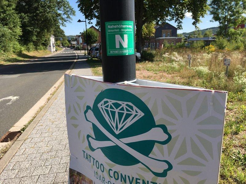 Grünes Hinweisschild an einem Laternenpfahl, das ist aber nicht die Markierung für den Nahesteig
